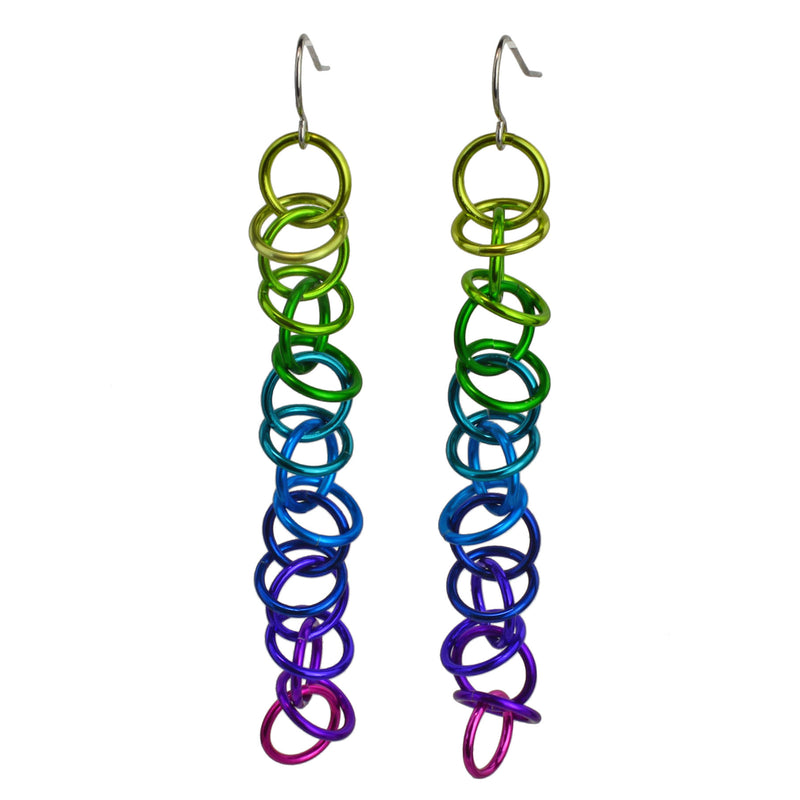 "Long earrings made of thin and colorful jump rings. The links are joined in a 1-1-1 chain, with additional loose rings ""orbiting"" around the main chain. The top color is chartruese, followed by green, teal, blue, purple, violet and bright pink."