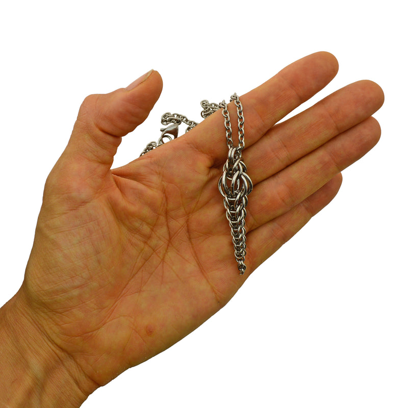 Auger Pendant by Rebeca Mojica held in hand to show scale. Pendant length equals about 3 fingers width.