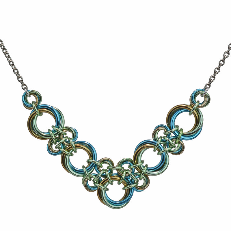 Chainmaille necklace made of 3-ring knots in a V shape in seafoam, light blue and champagne by Rebeca Mojica.