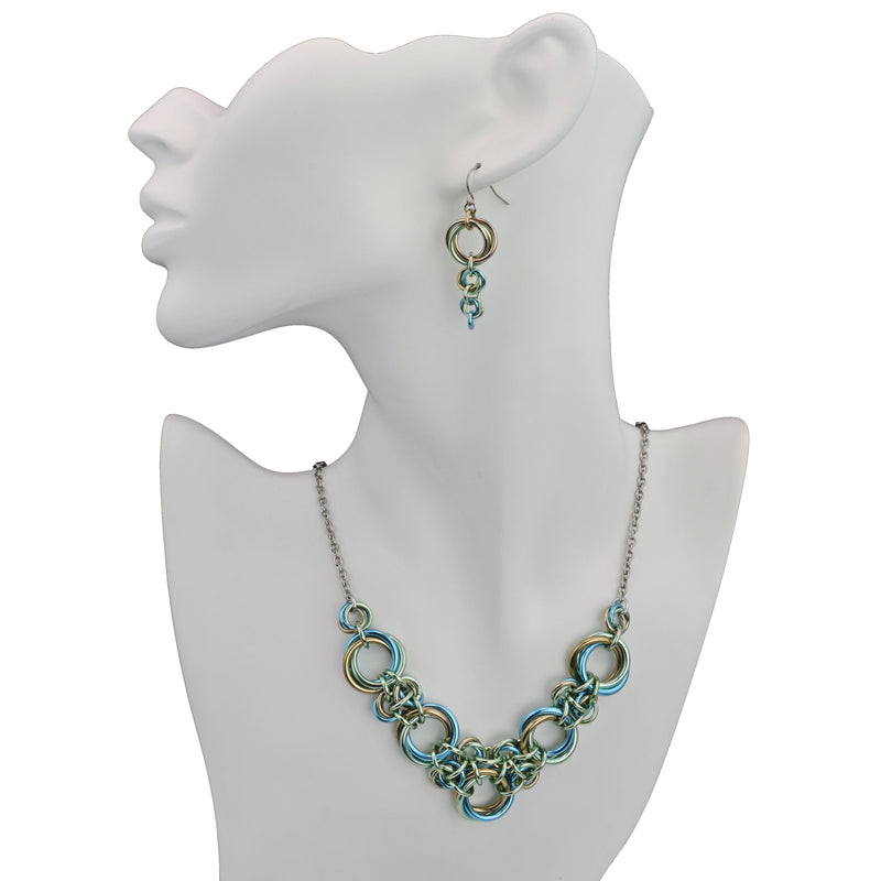 Chainmaile Knot necklace in V shape with coordinating earrings on white display form. Seashell colorway: seafoam, light blue and champagne.