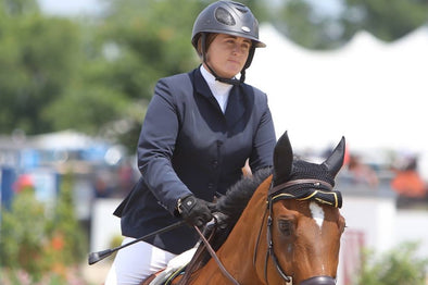 Victoria Colvin wearing a GPA helmet and Grand Prix Show coat riding a horse.
