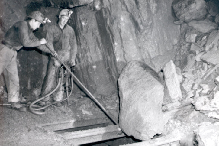 These miners are working in an underground chamber to prod broken ore down a chute, in preparation for transport. Year 1940. BMM #12543.