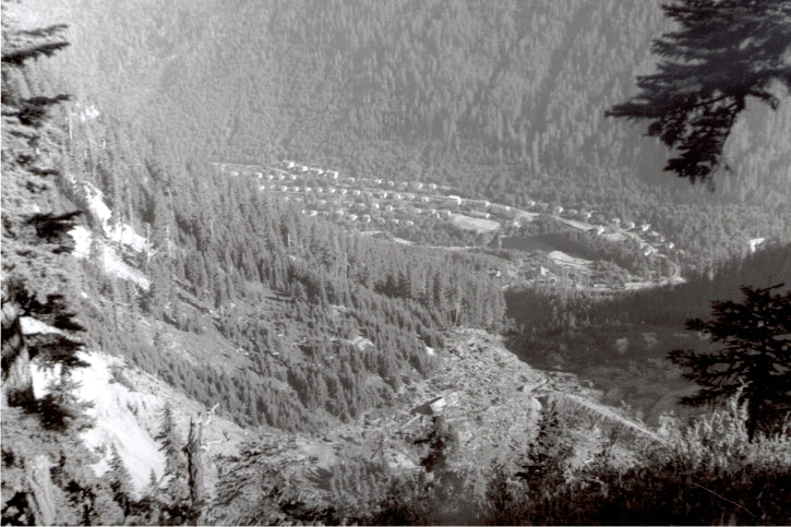 High in the mountains there were few good building sites except for a narrow valley floor. This was the only safe option for the Mount Sheer Townsite, built following the landslide that wiped out the Jane Camp in 1915. Year 1945. BMM #12560.