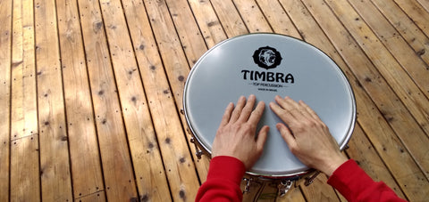 Timbal or timbau made by timbra, with hands on a wooden deck.