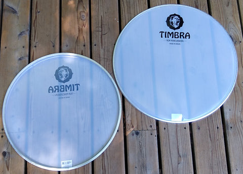 White plastic surdo head, translucent drum heads on wooden porch. Timbra logo visible.