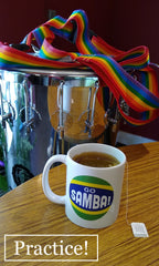 Mug of tea with Go Samba logo sitting on a table. Timbal and timbal strap in the background.