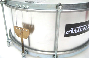 Aluminum snare drum used in samba reggae and maracatu. Brand is artcelsior. Silver drum shell and silver hardware view of the snare wires..