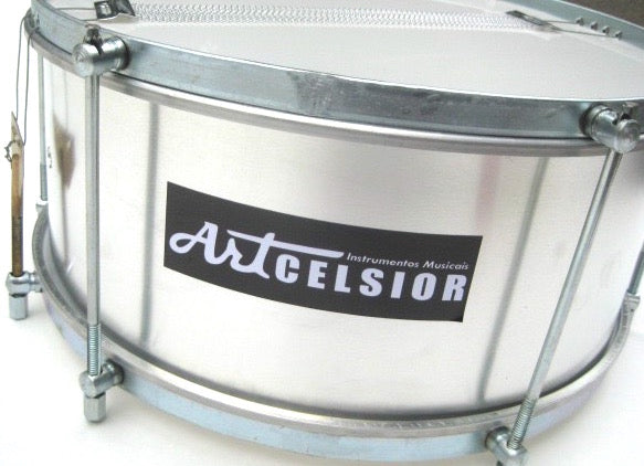 Aluminum snare drum used in samba reggae and maracatu. Brand is artcelsior. Silver drum shell and silver hardware.