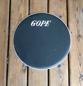 GOPE brand napa drum head, Black napa head with aluminum rim. Wood porch backdrop.