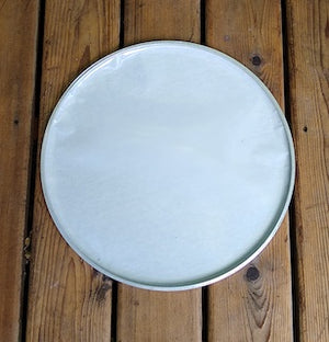 Bottom view of a GOPE drum head. White plastic interior of a napa head. Background of wood.