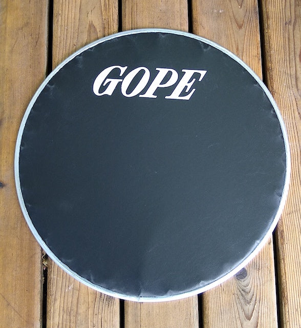 20 inch GOPE drum head for surdo. Black napa head on a wood backdrop