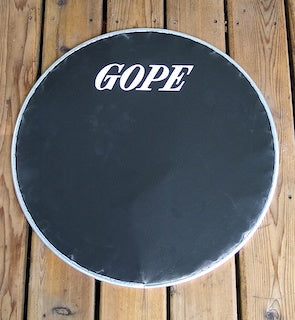 Black napa drum head on a wooden porch. Surdo head with aluminum rim and a GOPE logo
