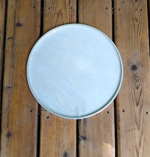 Back side view of a GOPE drum head made of napa. Sitting on a wooden porch.