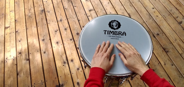 "14"" Timbra drum head on a timbal. Wooden deck background with hands resting on the drum head. Black timbra logo"