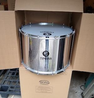 Surdo emerging from it's shipping box. Timbra logo on the surdo shell. Shiny aluminum, chrome hardware and 10 tuning rods.