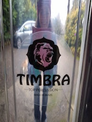 Timbra logo on the side of a polished aluminum surdo. You can see the photographer's reflection in the surdo shell.