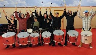 Samba Ja! with their new Timbra surdos. Seven surdos strapped on seven people with their arms raised.