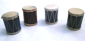 Four teeny hand-made shakers that look like little drums. All different colors in a white background.