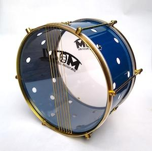 Brazilian drum with brass colored hardware, six strings, clear drum heads and a blue shell. The royal blue has small holes drilled into it.