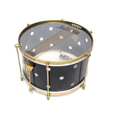 Black percussion instrument with brass colored hardware, six strings, clear drum heads and a black shell. The black drum shell has small holes drilled into it.