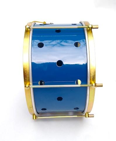 Batucada snare with brass colored hardware, six strings, clear drum heads and a blue shell. The blue shell has small holes drilled into it.