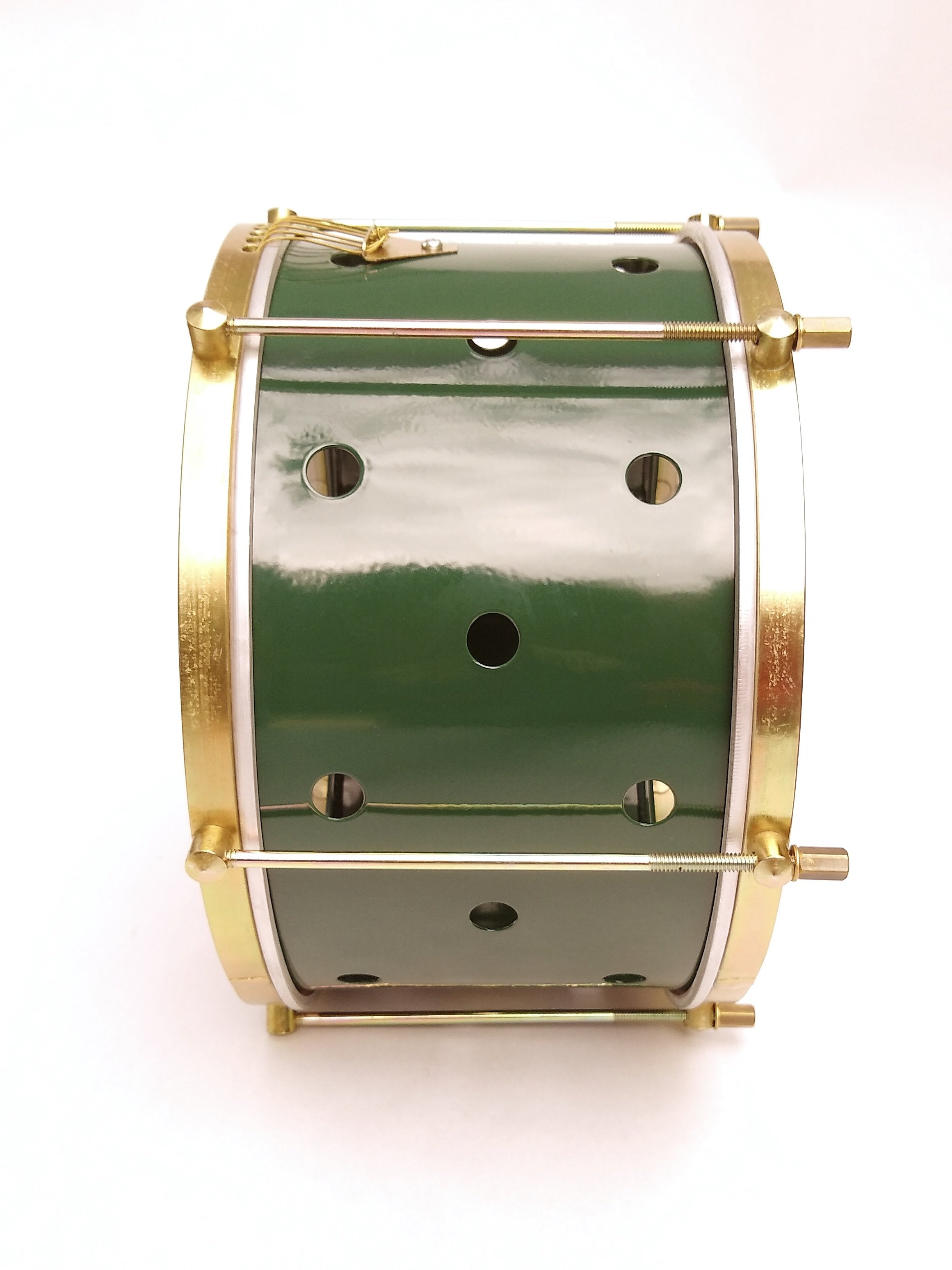 Brazilian batucada drum with brass colored hardware, six strings, clear drum heads and a green shell. The green shell has small holes drilled into it.