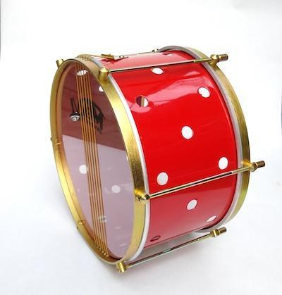 Samba snare with brass colored hardware, six strings, clear drum heads and a red shell sitting on it's side. The primary red drum shell has small holes drilled into it.
