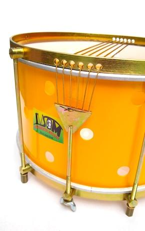 Brazilian caixa with brass colored hardware, six strings, clear drum heads and a yellow shell. The yellow body has small holes drilled into it.
