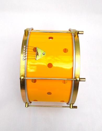Side view of an IVSOM Brazilian percussion instrument with brass colored hardware, six strings, clear dum heads and a yellow shell. The yellow has small holes drilled into it.