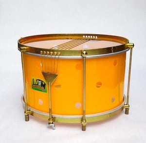 Brazilian snare with brass colored hardware, six strings, clear drum heads and a yellow shell. The primary yellow has small holes drilled into it.