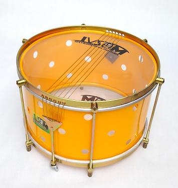 Drum from Brazil with brass colored hardware, six strings, clear drum heads and a yellow shell. The yellow shell has small holes drilled into it.