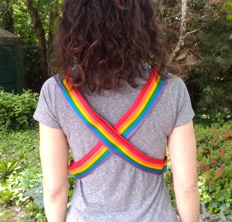 Crossed timbal straps across the back of the model. Rainbow strap.