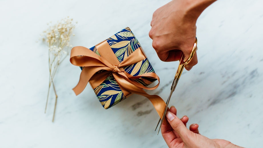 person cutting the ribbon on a wrapped gift with scissors