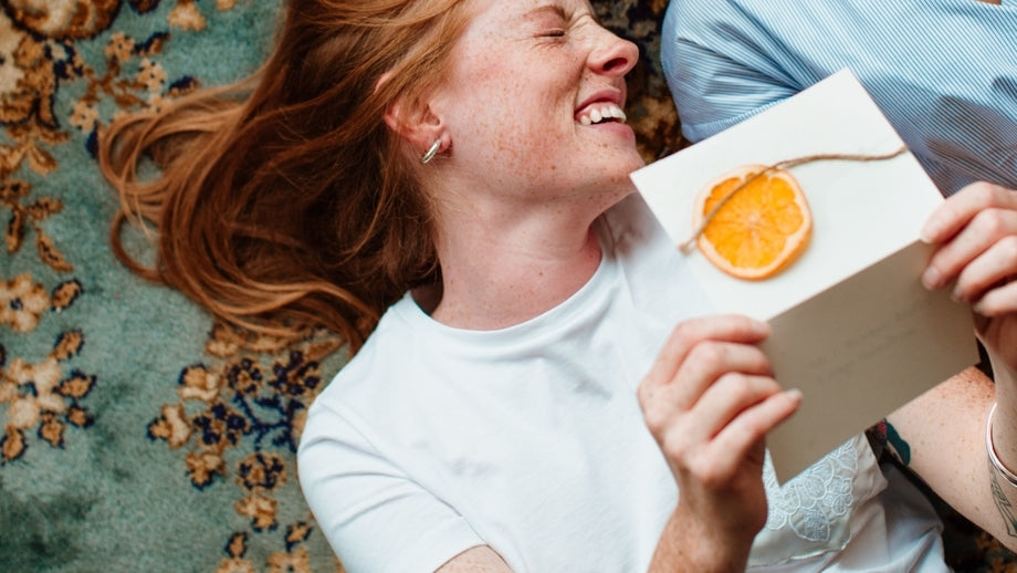 person with red hair smiling and holding a homemade card with an orange slice on it