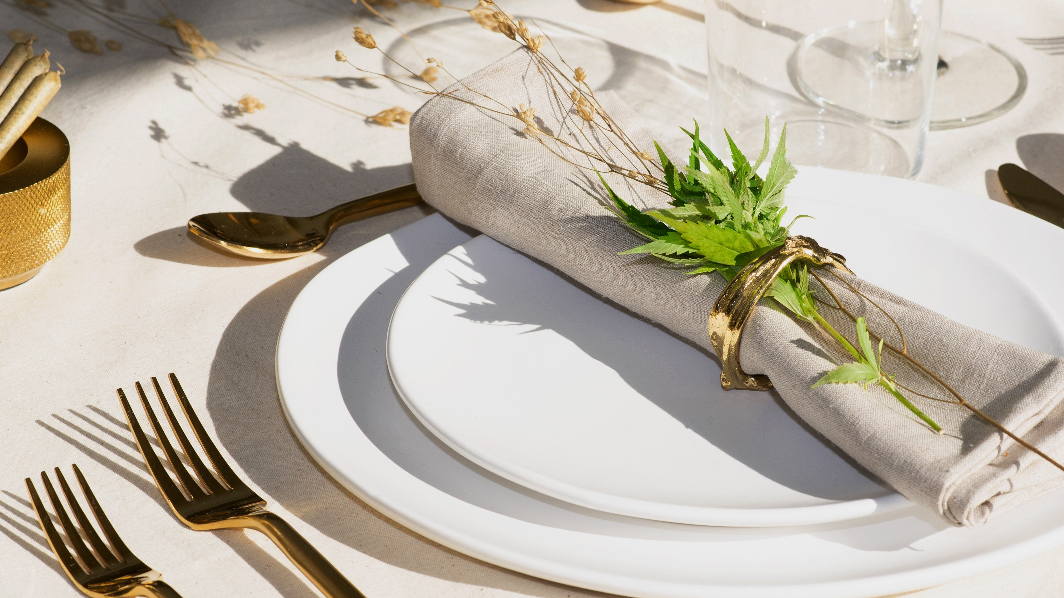 Beige napkin with cannabis leaf on it on top of two white plates. At table setting on beige table cloth with two gold forks beside the plates.