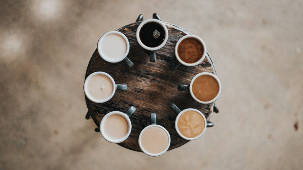 cups of coffee arranged in a circle on a wooden table
