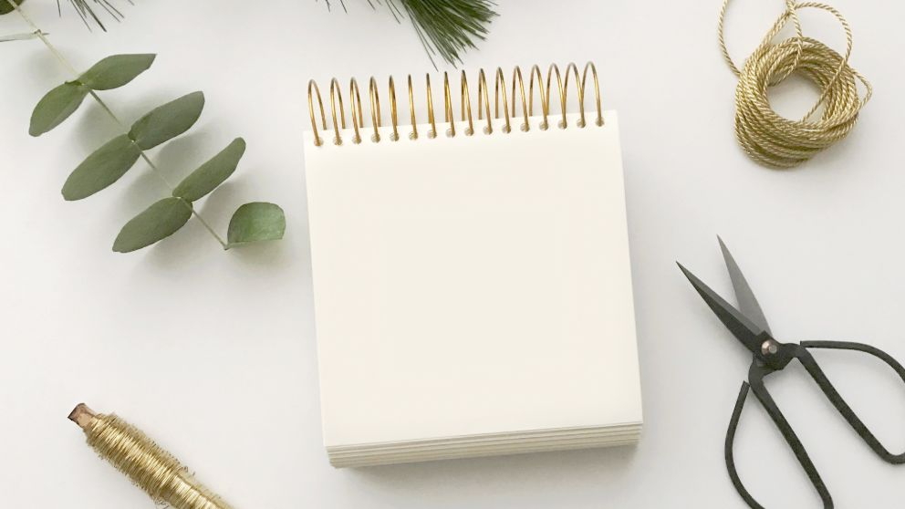 white spiral sketch pad on a while counter with craft materials