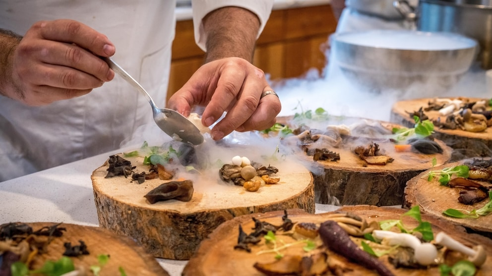 Chef plating fancy food on rustic log plates