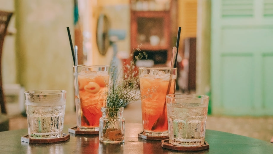 four drinks on a wooden table in a rustic kitchen