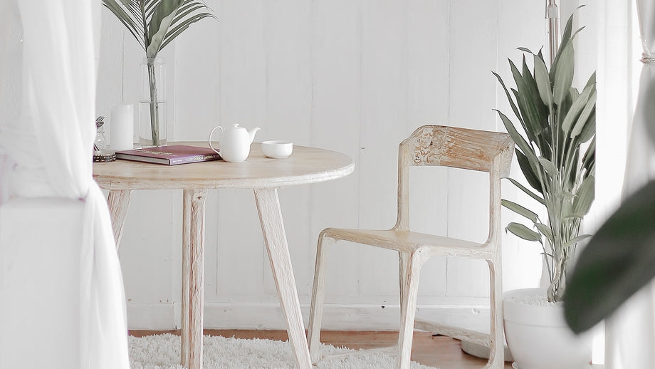a clean white room with a wooden table and chair decorated with green leafy plants