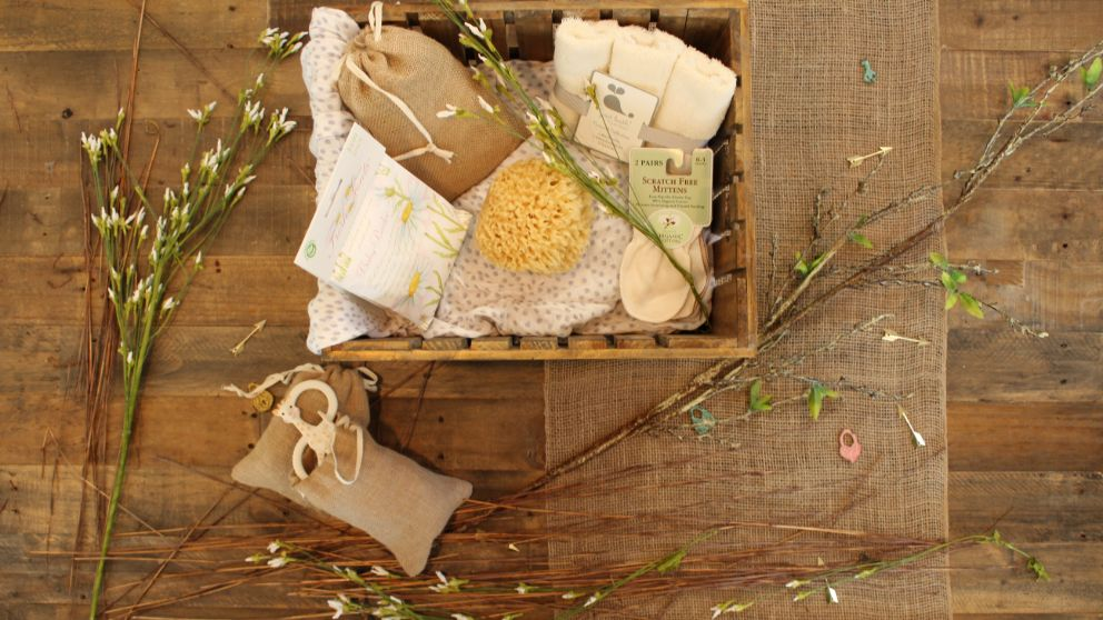 items needed for a home spa in a wooden basket with small flowers