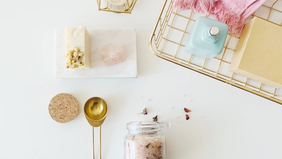 luxe beauty items used for an at-home spa artfully displayed on a white counter top