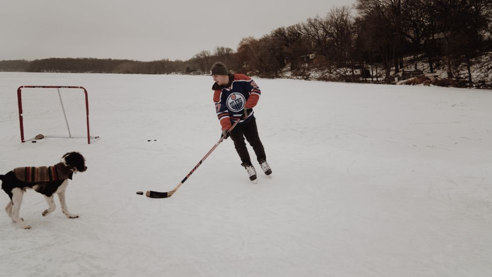 Person playing ice hockey on a frozen pond with a dog