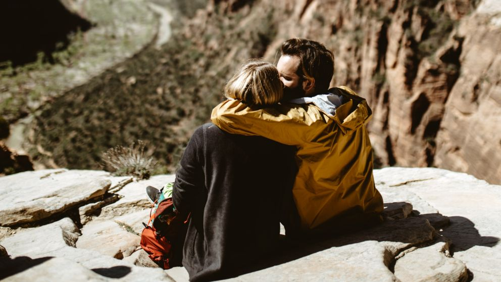 Couple cuddling looking out towards a cliff