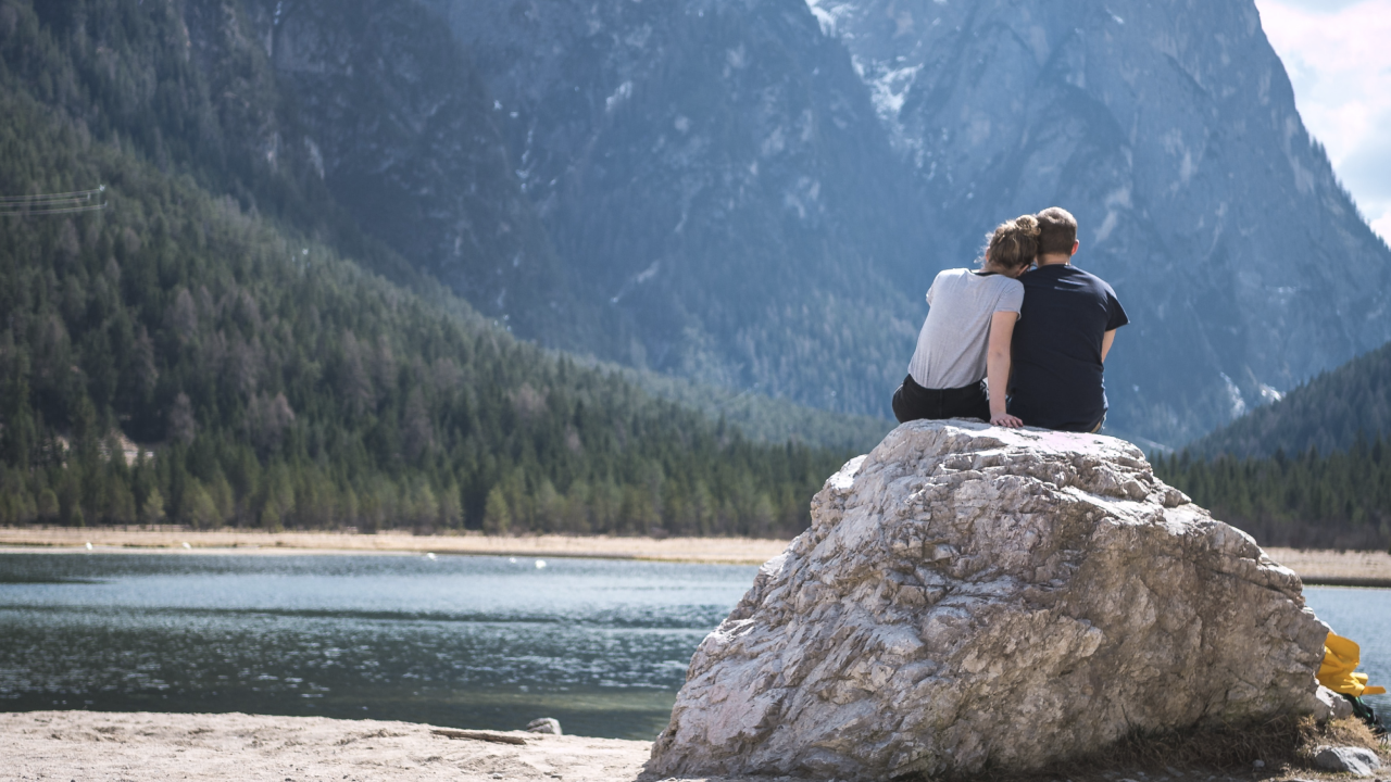 Couple looking out towards a beautiful lake reflecting the image of the forest and mountains around them