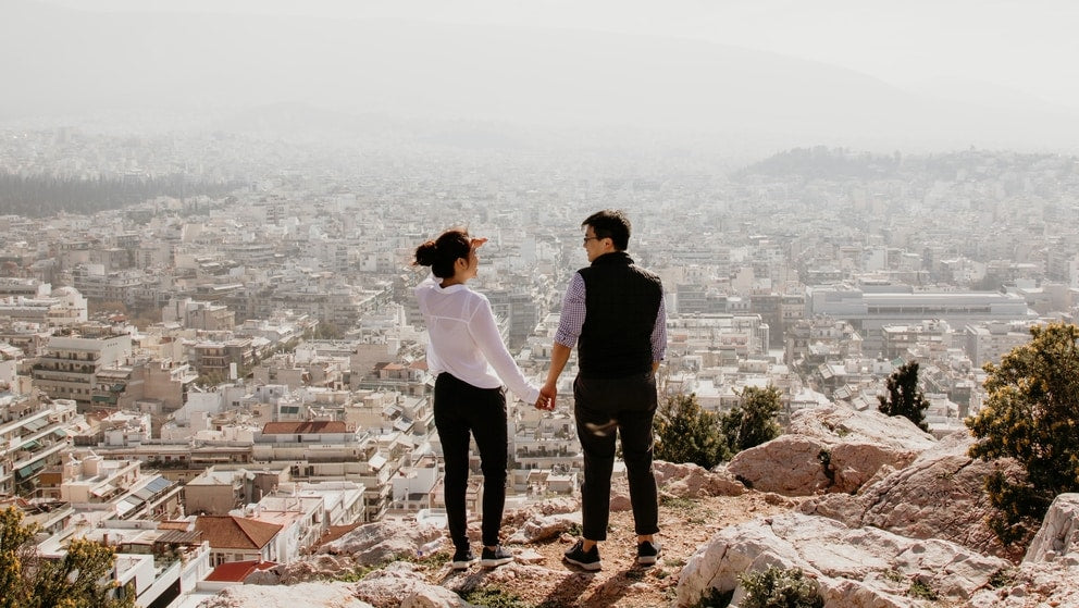 Couple abroad holding hands on a cliff over looking a city