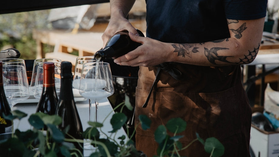 sommelier pouring wine from a bottle into a glass on an outdoor patio