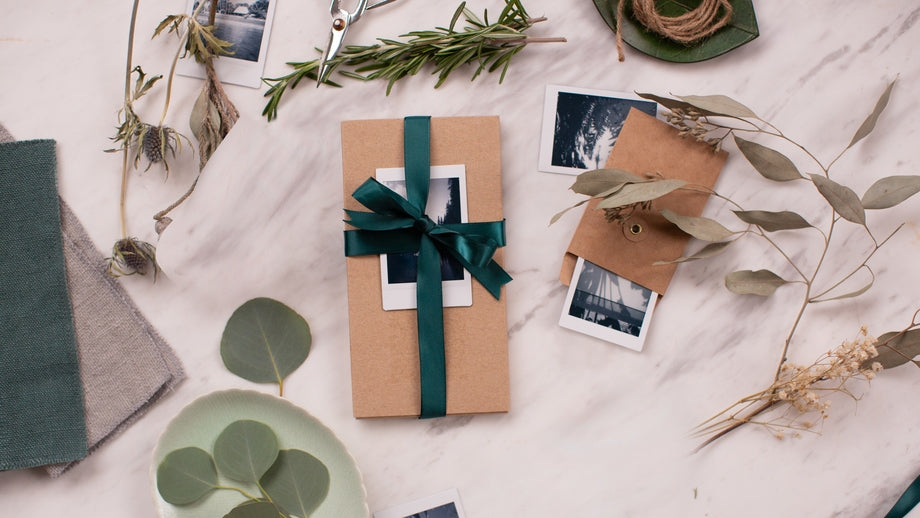 gift wrapped in brown paper with a green bow and Polaroid photograph attached