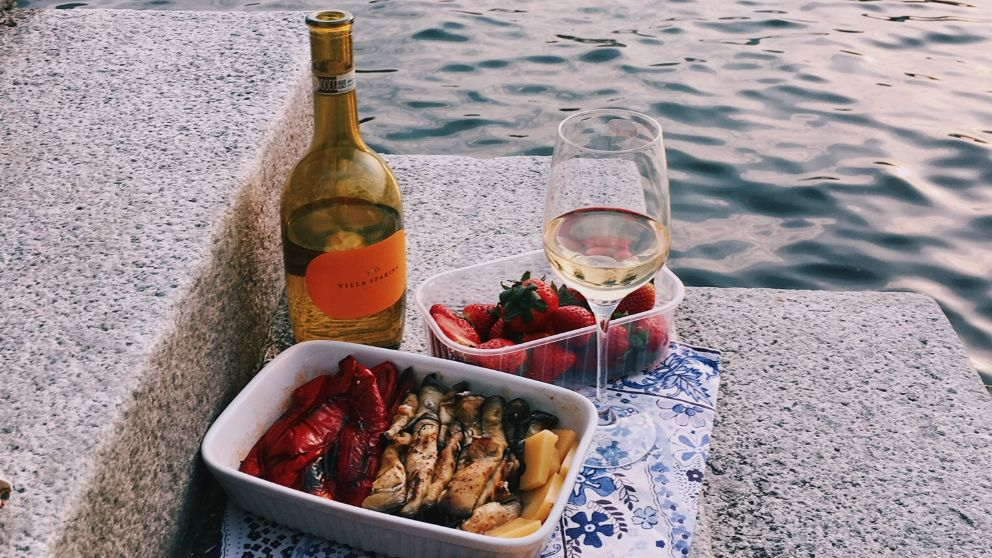 Wine and strawberries on steps by the water