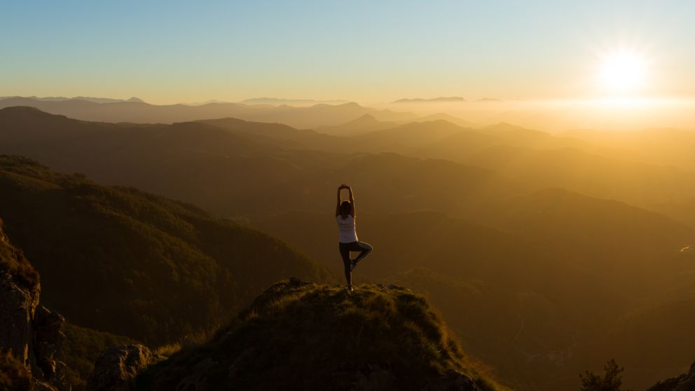 Person practicing yoga on a mountain looking out to a sunrise